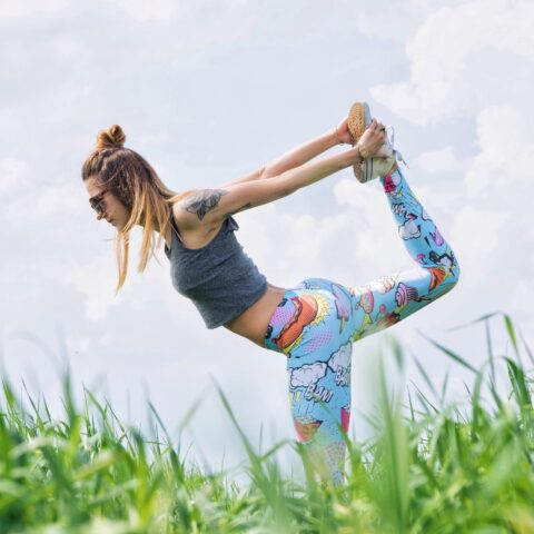 Girl stretching yoga in a field