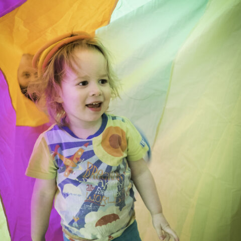 Child enjoying circus session surrounded by coloured parachute