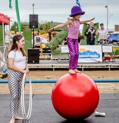 Girl balancing on a walking globe outside